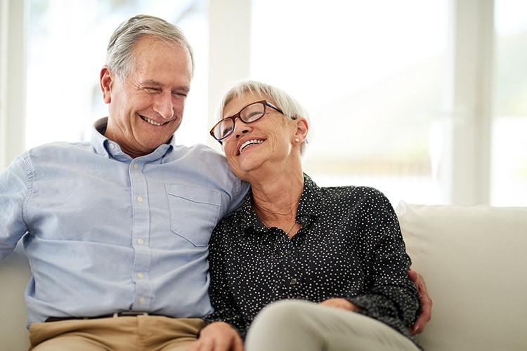 A senior couple enjoying a life settlement after selling their universal life insurance policy